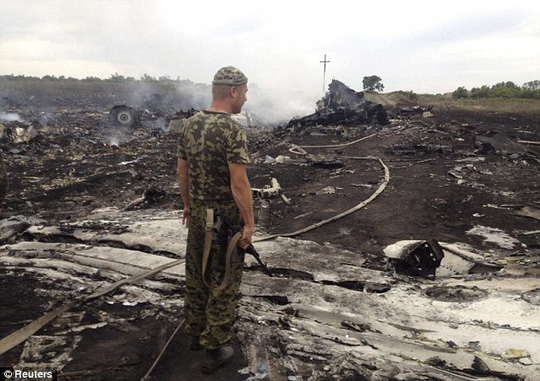 Destroyed: An armed pro-Russian separatist stands at a site of a Malaysia Airlines Boeing 777 plane crash in the settlement of Grabovo in the Donetsk region of Ukraine. It is claimed the flights black box has been recovered and will be sent to Moscow