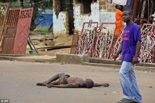 Shocking: Relatives of Ebola victims in Liberia have started dragging their loved ones bodies out of their homes and dumping them on the streets in a bid to avoid being quarantined. Above, a man walks past the dead body