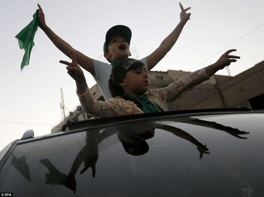 Cheerful: Young Palestinians are pictured celebrating the Egypt-brokered ceasefire, which was announced Palestinian President Mahmoud Abbas