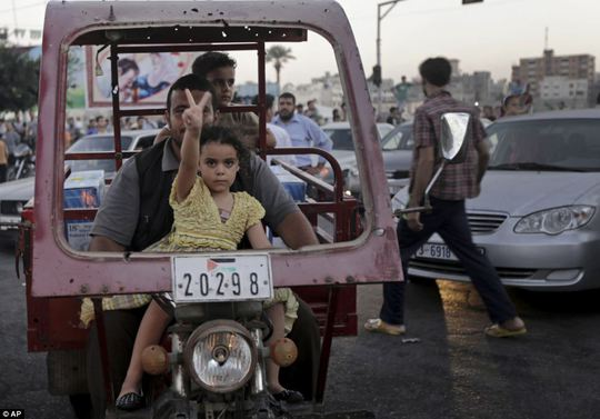 Young supporter: The truce took effect at 7 p.m. local time (1600 GMT). Above, a Palestinian girl makes the victory sign as she sits on her fathers lap yesterday