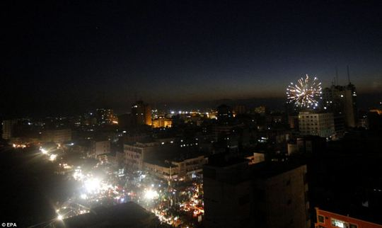 Fireworks: Palestinians set off fireworks as the gather in the streets after Israel and Hamas agreed what it was hoped would be a long-term truce