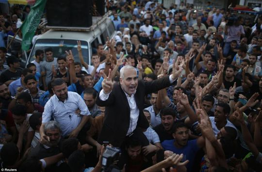Victorious: Hamas spokesman Fawzi Barhoum (centre) is carried by Palestinians as they celebrate what they said was a victory over Israel following the ceasefire