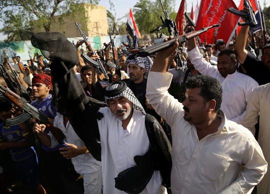 Chiến binh người Shiite giơ vũ khí phản đối ISIL tại thành phố Basra, cách thủ đô Baghdad 550 km hôm 16-6. Ảnh: AP