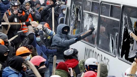 Người biểu tình tấn công hàng rào xe buýt do cảnh sát dựng lên. Ảnh: Reuters