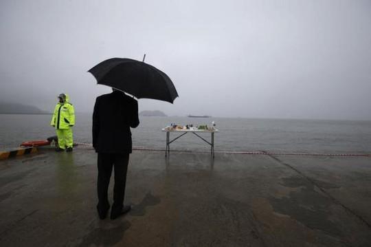 Một người đàn ông đứng trước một bàn thờ dành riêng cho các hành khách thiệt mạng và mất tích trên tàu Sewol hôm 28-4 ở cảng Jindo. Ảnh: Reuters
