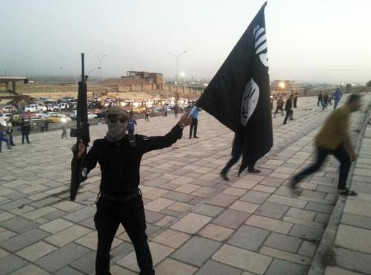 Một chiến binh IS vẫy cờ của tổ chức trên đường phố Mosul - Iraq ngày 23-6. Ảnh: Reuters