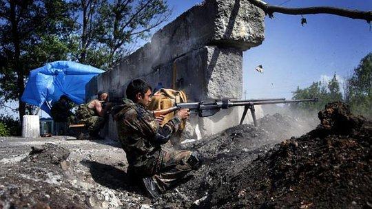 Một phiến quân ly khai thử vũ khí tại một trạm kiểm soát bên ngoài Slaviansk hôm 18-5. Ảnh: EPA