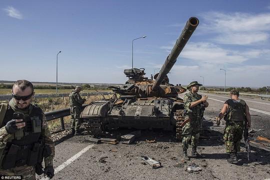 Các tay súng ly khai đứng cạnh một chiếc xe tăng của quân đội Ukraine bị phá hủy bên ngoài TP Luhansk. Ảnh: Reuters