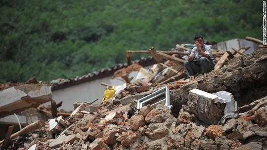 Một người đàn ông ngồi trên đống đổ nát sau trận động đất khủng khiếp hôm 3-8. Ảnh: Tân Hoa Xã
