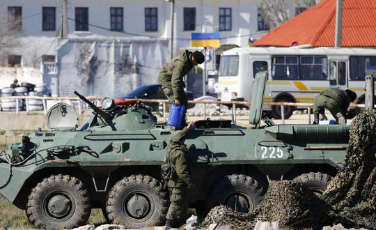 Binh sĩ Nga cùng xe bọc thép trước căn cứ hải quân Feodosia hôm 23-3. Ảnh: Reuters