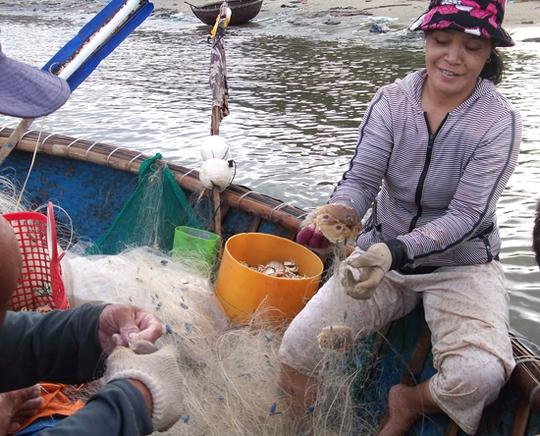 Chị Trần Thị Nhơn ở Sơn Trà phấn khởi phụ giúp chồng gỡ ghẹ sau chuyến ra khơi.