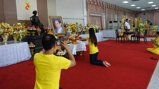 Người dân tỏ lòng tôn kính đối với Quốc vương trước bức chân dung của ông tại sảnh bệnh viện. Ảnh: ST
