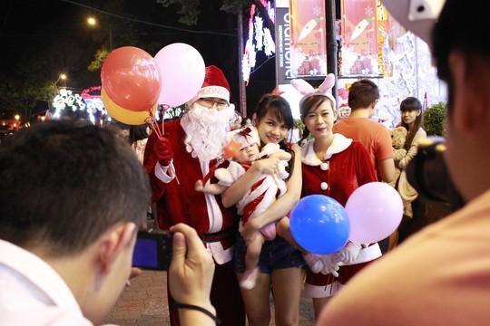 Các bạn trẻ mặc đồ đỏ của ông già Noel chụp ảnh lưu niệm