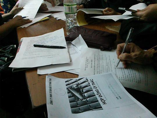 Các nhà đầu tư bày la liệt giấy tờ trên bàn để viết tường trình