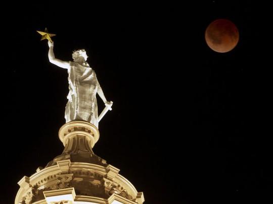 Mặt trăng trên đỉnh tượng Nữ Thần Tự Do ở Austin, Texas, Mỹ. Ảnh: Jay Janner/MCT