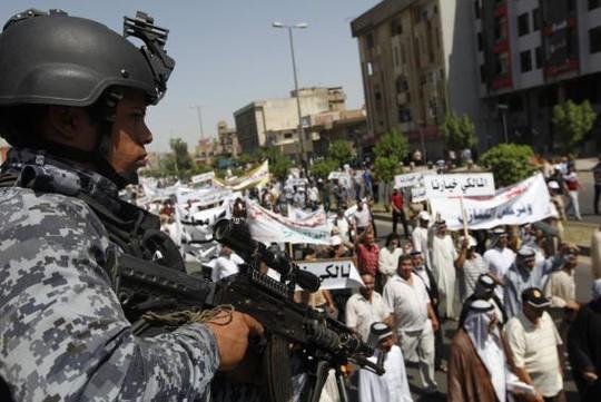Cảnh sát Iraq canh gác một cuộc biểu tình ủng hộ Thủ tướng Maliki ở Baghdad hôm 9-8. Ảnh: REUTERS
