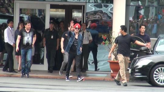 Kim Junsu (tóc đỏ) vẫy tay chào các fan Việt Nam khi ra khỏi cổng VIP sân bay Tân Sơn Nhất. Ảnh: Quốc Thắng