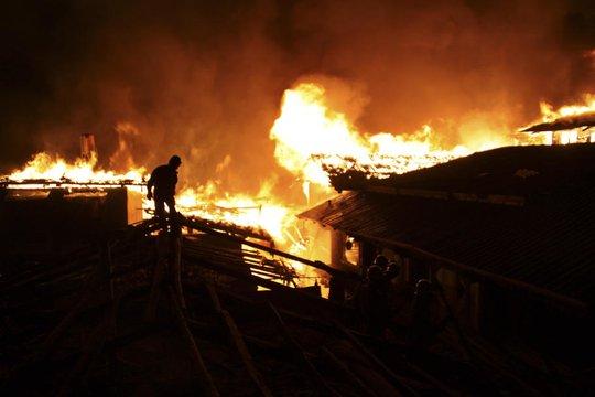 Đa số nhà đều bằng gỗ khiến lính cứu hỏa khó khăn trong việc dập lửa. Ảnh: AP