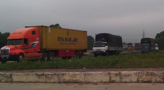 Xe tải nối đuôi nhau tiếp tục hành trình sau khi trạm cân nghỉ trưa.