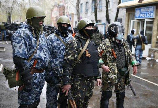 Các tay súng măc quân phục không phù hiệu bên ngoài trụ sở cảnh sát ở Slaviansk ngày 13-4... Ảnh: Reuters