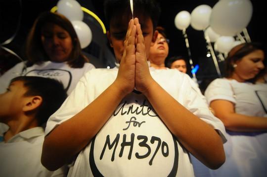 Người Malaysia cầu nguyện cho hành khách trên chuyến bay ở Kuala Lumpur. Ảnh: AP