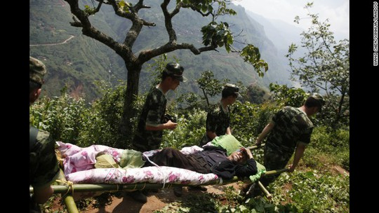 Binh sĩ Trung Quốc và nhân viên cứu hỏa vận chuyển các nạn nhân ra khỏi hiện trường. Ảnh: AP, Tân Hoa Xã