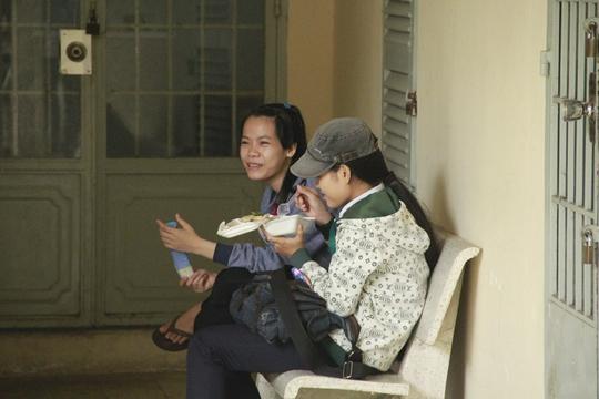 """""""Ở quê gia đình khó khăn lên đây thi vỏn vẹn chỉ có 300.000 đồng, cho 3 ngày thi nên mình tranh thủ ăn cơm chay miễn phí tại trường"""", bạn Oanh (trong hình đội nón) cho biết."""