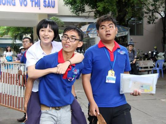Em Đinh Thị Thùy Linh (19 tuổi, huyện Eakar, Đắk Lắk) bị tàn tật không thể đi lại, được các bạn tình nguyện viên cõng ra vào phòng thi.