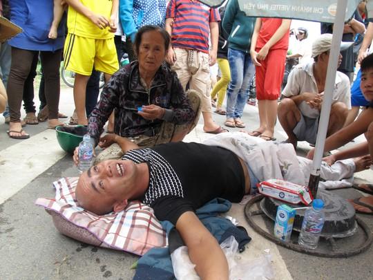 Ông Trương Văn Dũng, vừa lăn lộn dưới đường vừa luôn miệng quát tháo, nói nhảm.