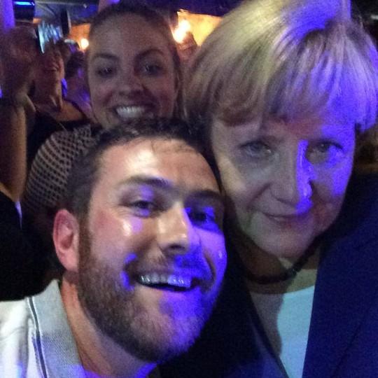Thủ tướng Đức Angela Merkel chụp hình với người dân TP Brisbane - Úc tối 14-11. Ảnh: Twitter