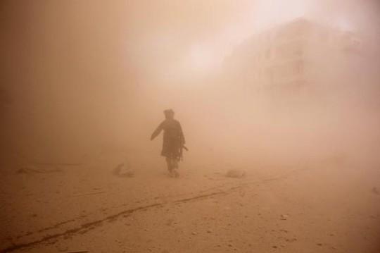 Một phiến quân nổi dậy Syria băng qua khu vực vừa bị ném bom ở TP Aleppo. Ảnh: Reuters
