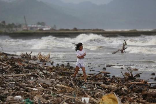 Một bé gái đi dọc bờ biển tỉnh Quezon hôm 6-12, thời điểm bão Hagupit vừa tràn qua. Ảnh: AP