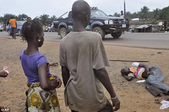 Một bệnh nhân mắc Ebola nằm bên vệ đường ở Liberia. Ảnh: AP