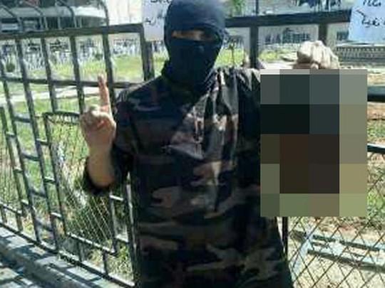 Abdel-Majed Abdel Bary cầm thủ cấp một binh sĩ không xác định bị cắt rời. Ảnh: Courier Mail
