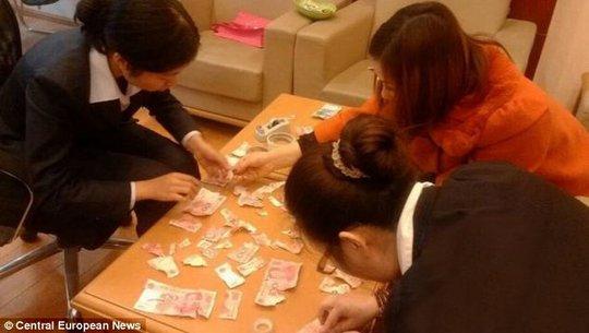 Gia đình cậu bé cố gắng ráp những mảnh tiền lại với nhau. Ảnh: Central European News