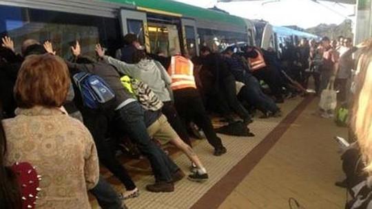Hơn 50 hành khách đẩy xe lửa nghiêng về một bên cứu người đàn ông. Ảnh: News.com.au