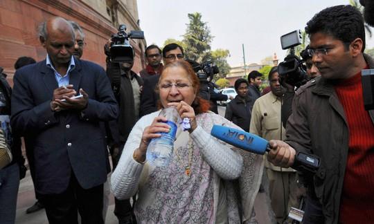 Nữ nghị sĩSumitra Mahajan vội vã uống nước sau khi thoát khỏi cuộc loạn đả. Ảnh: Reuters