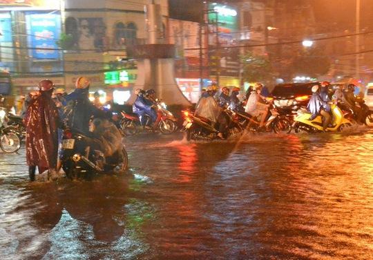 Khu vực ngã tư Tân Phong cũng bị ngập sâu trong nước khiến xe máy qua lại nơi đây nhiều xe bị chết máy (K.Giới)