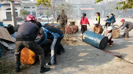 Người dân giúp chủ xưởng nến đưa thùng phuy dầu và một số tài sản khác ra khỏi xưởng nến