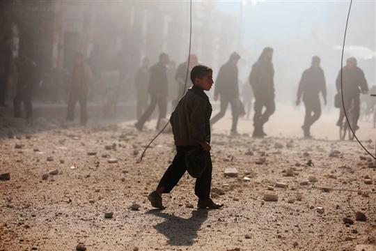 Một cậu bé đi gần một khu vực bị tàn phá bởi trận pháo kích  của lực lượng trung thành với Tổng thống Syria Bashar Assad tại Duma, Damascus hôm 22-12. Ảnh: Reuters