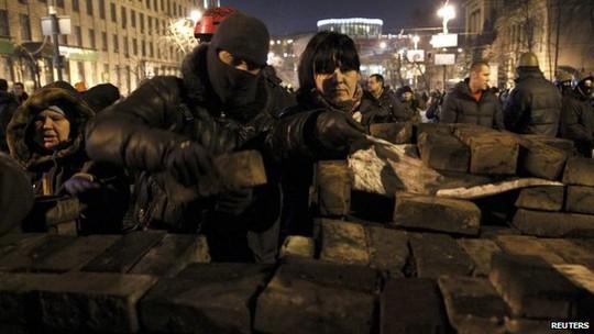...người biểu tình tiếp tục dựng rào chắn. Ảnh: Reuters