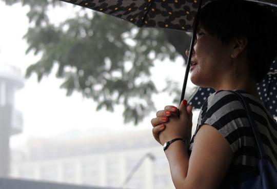 Một người dân đứng ngắm Thương xá ngày cuối cùng trong con mưa rào.