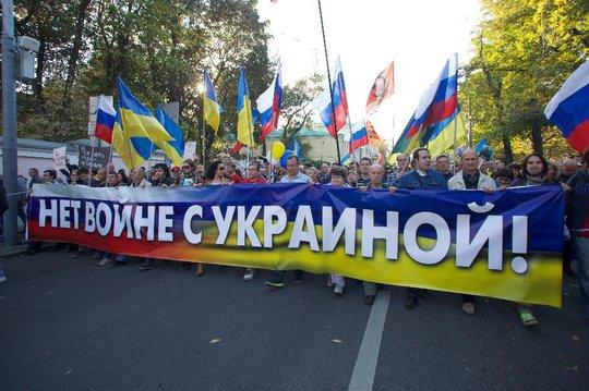 Người biểu tình mang cờ Ukraine, trang trí băng-rôn với khẩu hiệu để phản đối Nga can thiệp vào Ukraine. Ảnh: AP