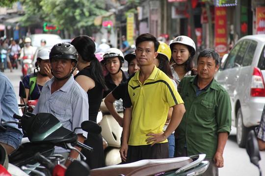 Dãy người xếp hàng tràn cả ra lòng đường. Nhiều người vẫn đôi nguyên mũ bảo hiểm để nhanh chân xếp hàng chờ tới lượt.