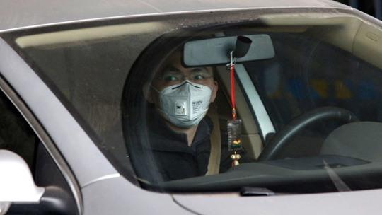 Ngồi trong xe hơi, người đàn ông vẫn phải bịt khẩu trang. Ảnh: Reuters