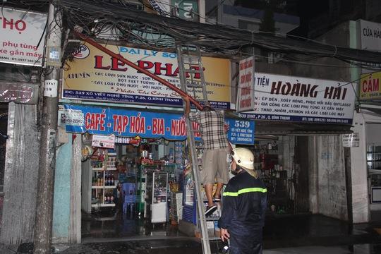 Lực lượng PCCC đang tháo dỡ, mang những vật dụng dễ cháy trong cửa hàng ra ngoài