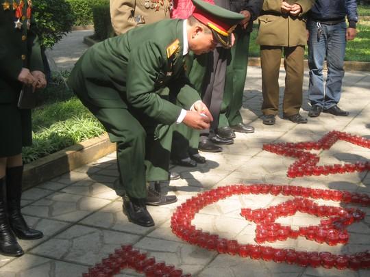 Bác Vũ Văn Anh và những thành viên trong đoàn rất say sưa tỷ mỷ công trình bằng nến để tri ân Đại tướng Võ Nguyên Giáp