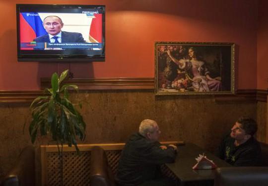 Người dân Kiev theo dõi cuộc họp báo của Tổng thống Nga Putin hôm 4-3. Ảnh: Reuters
