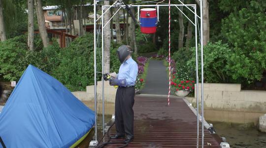 Gates bước đến giá treo và giật dây cho xô nước đổ ụp xuống đầu. Ảnh: Business Insider