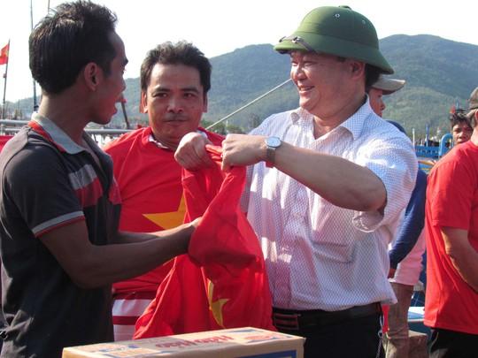 Đại diện Hội Doanh nghiệp quận Hải Châu, TP Đà Nẵng trao áo mang màu cờ đỏ sao vàng cho ngư dân trước khi ra khơi